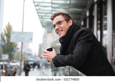 Smiling business man in glasses near the office. side view