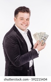 smiling business man holding up cash money against white background. monew and win concept.