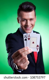 Smiling business man holding a pair of  aces against a white background