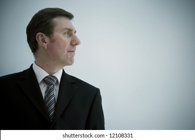 A smiling business man landscape orientation with copy space to the right. profile looking out of frame