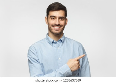 Smiling business man pointing right with index finger and looking at camera, isolated on gray background