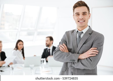Smiling Business man standing with arms crossed in office with colleagues by the table on background