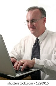 smiling business man typing and working on laptop computer; shot on white background