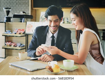 Smiling business man and woman have a meeting and looking at smart phone in modern cafe.