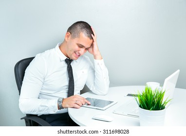 smiling business man working in the office using tablet computer
