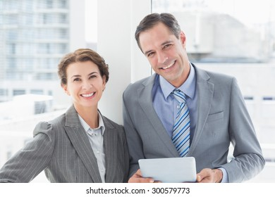 Smiling business partners looking at camera in an office