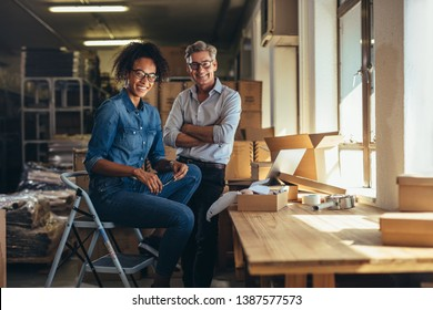 Smiling business partners together at online seller warehouse. Young woman and mature man looking at camera and smiling at drop shipping business office.
