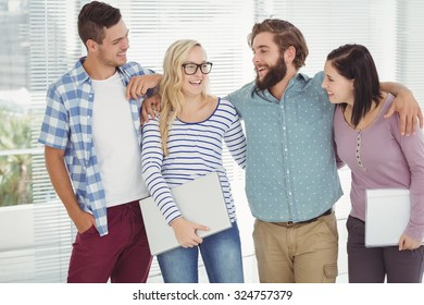 Smiling business people with arm around while standing at office