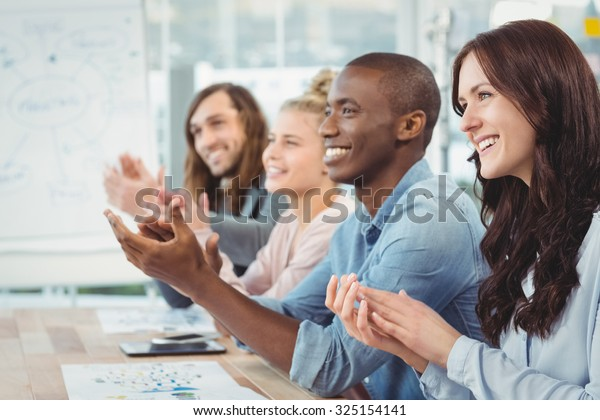 Smiling business people clapping at desk in office