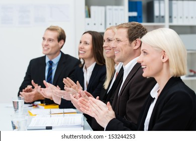 Smiling business people clapping their hands at the end of a meeting or presentation or in recognition of an achievement by one of their colleagues