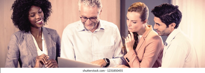 Smiling business people discussing over laptop in office