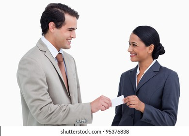 Smiling business people exchanging business cards against a white background