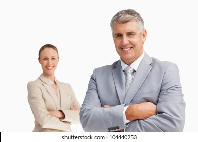 Smiling business people with folded arms against white background