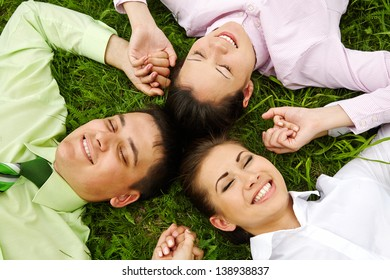 Smiling business people lying on grass and holding by hands