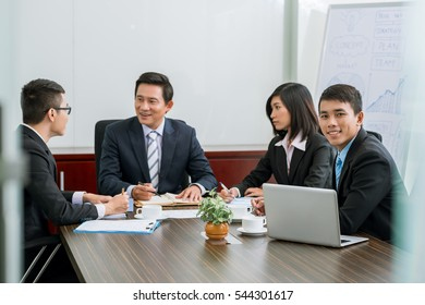 Smiling business people negotiating at table in meeting room