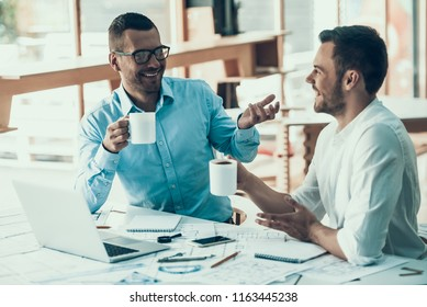 Smiling Business People on Coffee Break in Office. Two Yong Colegues Chatting while drinking Coffee at Work. Coworkers Sitting at Desk and having Coffe break. Corporate Lifestyle Concept.