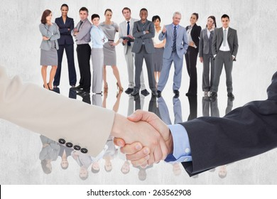 Smiling business people shaking hands while looking at the camera against white background