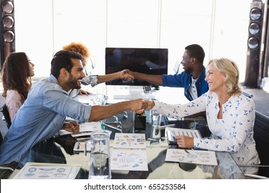 Smiling business people shaking hands during meeting at creative office