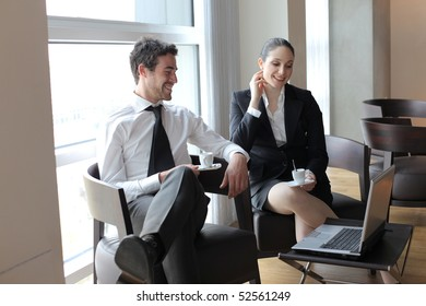 Smiling business people sitting in a lounge