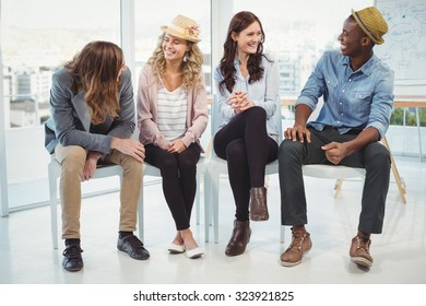 Smiling business people sitting on chair in office