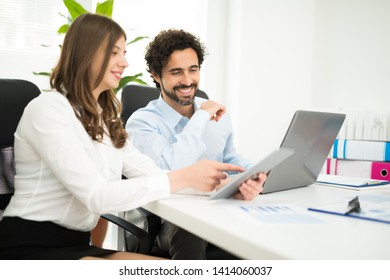 Smiling business people using a laptop computer in their office. Shallow depth of field, focus on the man