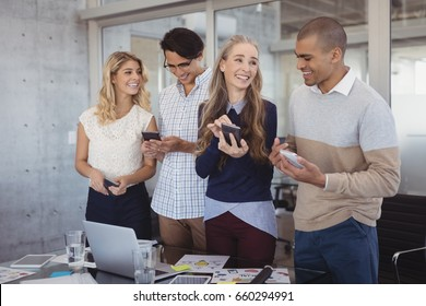 Smiling business people using mobile phones in creative office