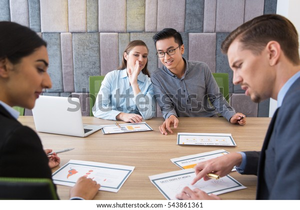Smiling business people whispering at meeting