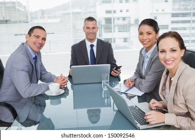 Smiling business people working together with their laptop in bright office