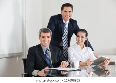 Smiling business team with laptop computer and clipboard in the office