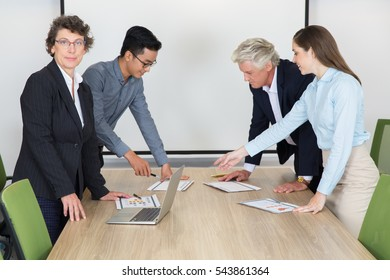 Smiling business team looking at paper in office