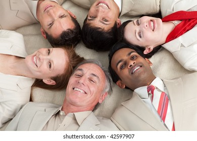 Smiling business team lying in a circle with heads together