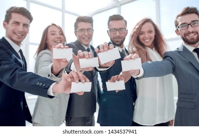 smiling business team showing their business cards.