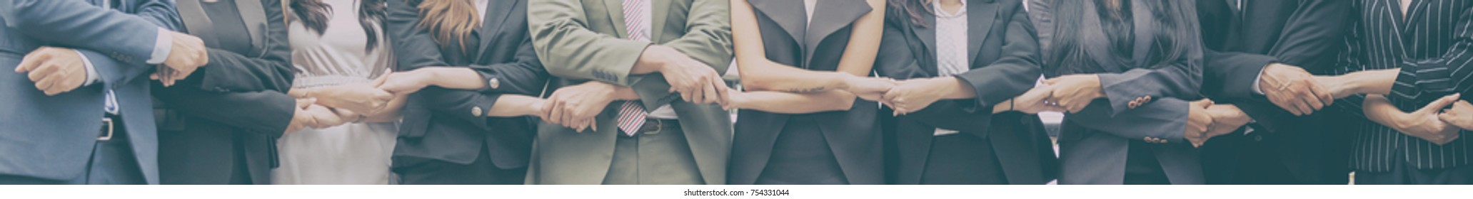 Smiling business team standing upright with holding hands. Mixed race business team concepts.