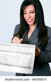 A smiling business woman checking the finance, bonds, shares, securities,  pages of a national newspaper.  Company data has been blurred for privacy