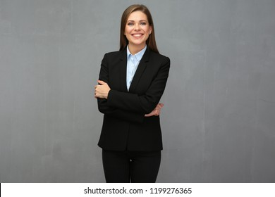 Smiling business woman with crossed arms in front of grey wall.