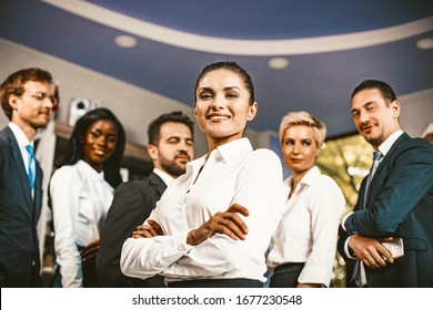 Smiling Business Woman Crossed Her Arms While Standing Against Backdrop Of Business Team, Positive Caucasian Woman Standing In Front Of Team On Blurred Back, Toned Image