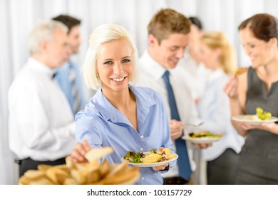Smiling business woman during company lunch buffet hold salad plate