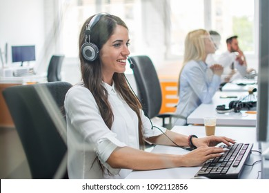 Smiling business woman with hands-free set working on computer and giving instructions online to customer.