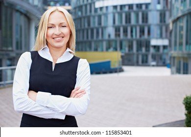 Smiling business woman with her arms crossed outside the office