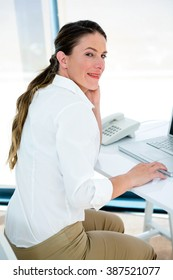 smiling business woman, at her desk typing on her laptop
