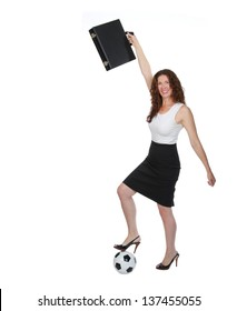 Smiling business woman holding a briefcase overhead with one foot on a soccerball.
