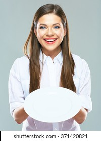 Smiling Business woman  holding empty white plate in front. Studio isolated portrait of young business woman.