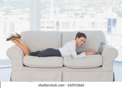 Smiling business woman lying on couch with laptop