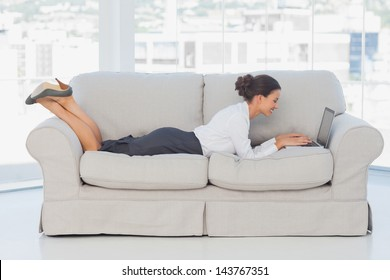 Smiling business woman lying on couch using laptop