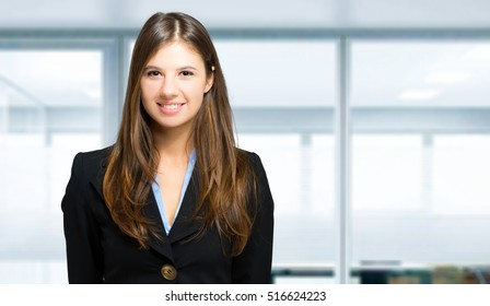 Smiling business woman in a modern office wearing a business suit