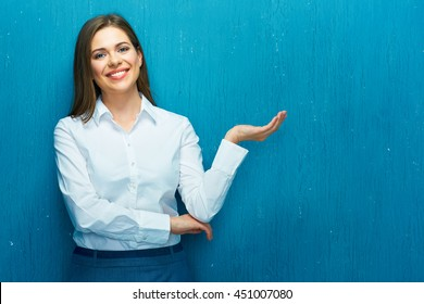 Smiling business woman presenting empty hand with your product. White shirt. Blue wall.