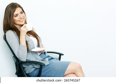 Smiling Business woman relaxed with coffee cup sitting in office chair. Isolated portrait.