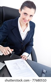 smiling business woman or secretary putting stamp on a document
