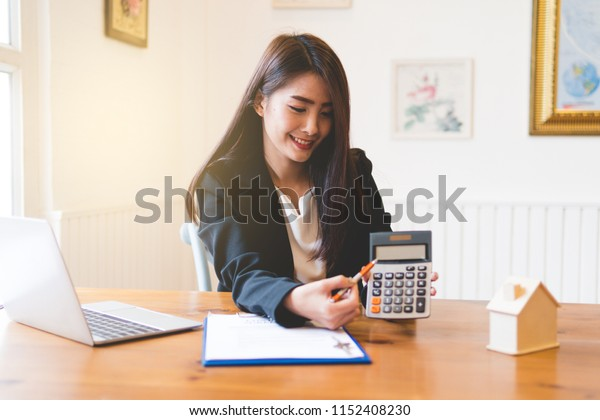 smiling business woman showing the calculator in office
