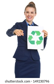 Smiling business woman showing recycle sign and pointing in camera
